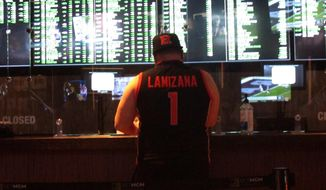 A man makes a sports bet at the Borgata casino in Atlantic City NJ on Friday March 19, 2021, the first full day of the NCAA March Madness tournament.  Last year, it was March sadness as the NCAA college basketball tournament got canceled days before it was supposed to start, due to the coronavirus. (AP Photo/Wayne Parry)