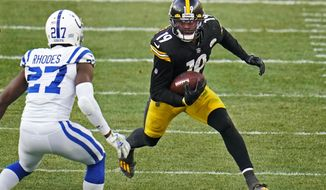 """File-This Dec. 27, 2020, file photo shows Pittsburgh Steelers wide receiver JuJu Smith-Schuster (19) running after a catch with Indianapolis Colts cornerback Xavier Rhodes (27) defending during the second half of an NFL football game in Pittsburgh. Smith-Schuster is keeping it """"lit"""" with the Pittsburgh Steelers. The free-agent wide receiver surprisingly opted to return to the Steelers on Friday just days after strongly hinting that his departure on the open market was imminent. (AP Photo/Gene J. Puskar, File)"""