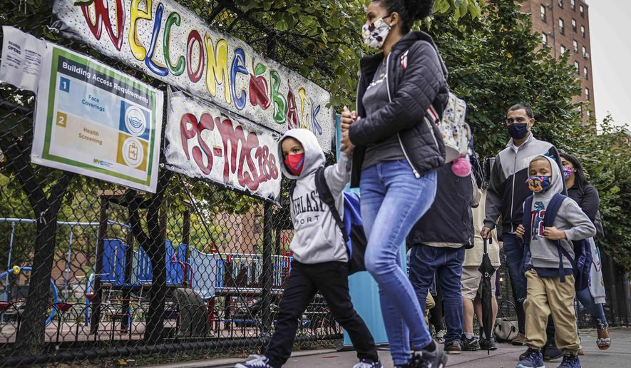 FILE - In this Sept. 29, 2020, file photo, students arrive with their guardians for in-person classes at Public School 188 in New York. New York City public school students will get another chance to go back to school in-person this spring after federal authorities eased their guidance on how many children can safely fit in a classroom. (AP Photo/John Minchillo, File)