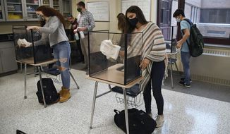 Students in teacher Christopher Duggan's science class clean their work areas at the end of class at Windsor Locks High School in Windsor Locks, Conn. (AP Photo/Jessica Hill, File)