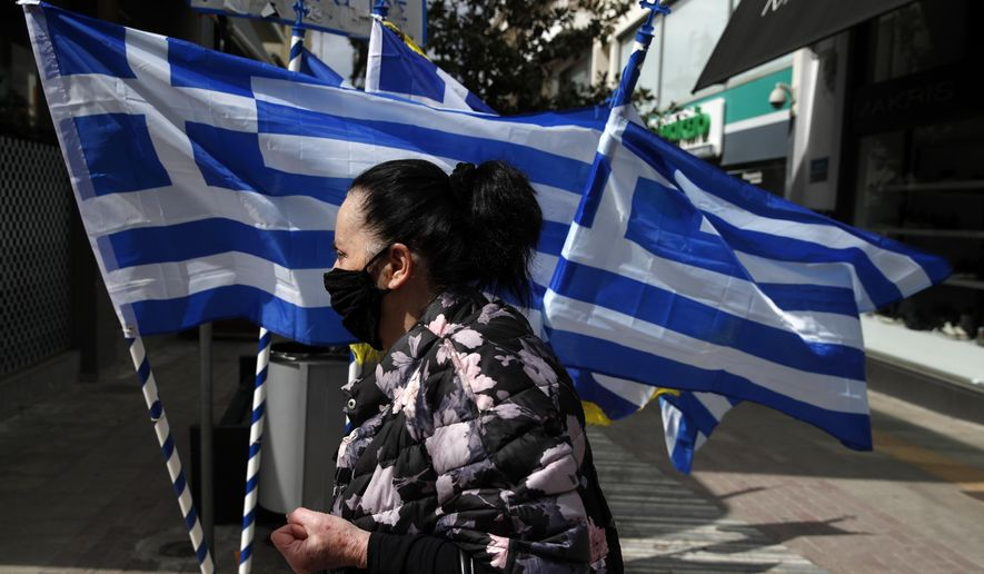 A woman wearing a face mask against the spread of coronavirus, walks in front of Greek flags which are for sale in Athens, Friday, March 19, 2021. The military parade on March 25, marking 200-years since the war that resulted in Greece's independence from the Ottoman Empire and rebirth as a nation, will be held without spectators due to the coronavirus, and only Greek and foreigners political officials will attend it. (AP Photo/Thanassis Stavrakis)