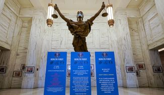 A Lady Justice statue with a face mask stands behind panels announcing COVID-19 protocols at an entrance to a Manhattan federal courthouse, Friday, March 12, 2021, in New York. On April 27, 2021, DHS Secretary Alejandro Mayorkas ordered ICE and Border Patrol agents to stop arresting people near state and federal courthouses unless there's an overwhelming national security or public safety reason for doing so.  (AP Photo/Mary Altaffer)