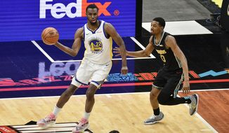 Golden State Warriors forward Andrew Wiggins (22) handles the ball against Memphis Grizzlies guard De'Anthony Melton (0) in the first half of an NBA basketball game Friday, March 19, 2021, in Memphis, Tenn. (AP Photo/Brandon Dill)