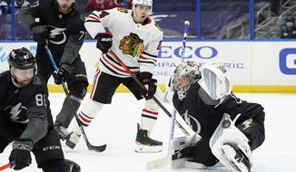 Tampa Bay Lightning goaltender Andrei Vasilevskiy (88) makes a pad save on a deflection by Chicago Blackhawks center Pius Suter (24) during the first period of an NHL hockey game Saturday, March 20, 2021, in Tampa, Fla. Defending for Tampa Bay is defenseman Erik Cernak (81). (AP Photo/Chris O'Meara)