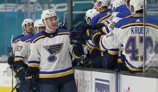 St. Louis Blues defenseman Vince Dunn, left, is congratulated by teammates after scoring against the San Jose Sharks during the first period of an NHL hockey game in San Jose, Calif., Saturday, March 20, 2021. (AP Photo/Jeff Chiu)