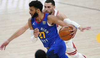 Denver Nuggets guard Jamal Murray, front, drives past Chicago Bulls guard Zach LaVine in the second half of an NBA basketball game Friday, March 19, 2021, in Denver. (AP Photo/David Zalubowski)