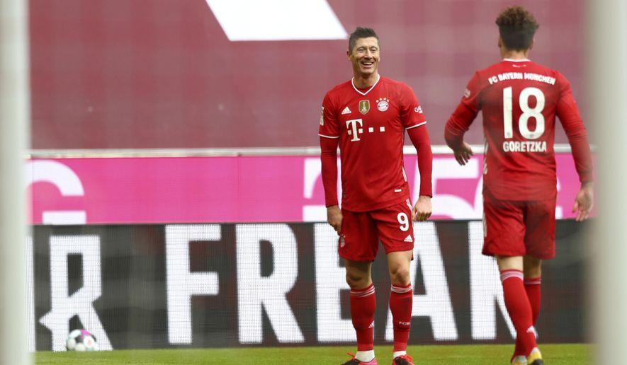 Bayern's Robert Lewandowski, left, celebrates with Bayern's Leon Goretzka after scoring his sides third goal during the German Bundesliga soccer match between FC Bayern Munich and VfB Stuttgart in Munich, Germany, Saturday, March 20, 2021. (Matthias Schrader/Pool via AP)