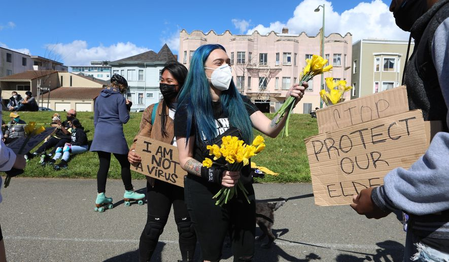 Organizer Ashley Silva distributes flowers to folks attending a rally organized in solidarity against racist violence against Asian Americans at Madison Park on Saturday, March 20, 2021 in Oakland, Calif. (Yalonda M. James/San Francisco Chronicle via AP)