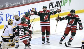 New Jersey Devils right wing Kyle Palmieri (21) celebrates his goal with Sami Vatanen (45), Jack Hughes (86) and P.K. Subban (76) as Pittsburgh Penguins right wing Bryan Rust (17) and goaltender Casey DeSmith (1) react during the first period of an NHL hockey game Saturday, March 20, 2021, in Newark, N.J. (AP Photo/Bill Kostroun)