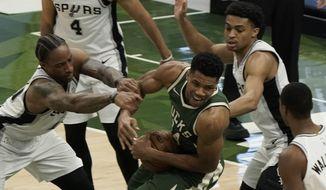 Milwaukee Bucks' Giannis Antetokounmpo is fouled during the second half of an NBA basketball game against the San Antonio SpursSaturday, March 20, 2021, in Milwaukee. (AP Photo/Morry Gash)