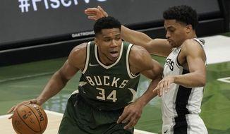 Milwaukee Bucks' Giannis Antetokounmpo tries to drive past San Antonio Spurs' Keldon Johnson during the second half of an NBA basketball game Saturday, March 20, 2021, in Milwaukee. (AP Photo/Morry Gash)