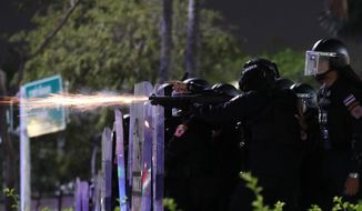 Sparks fly from the barrel of a gun used by riot police to disperse protesters who removed container vans used as a barricade in front of the Grand Palace Saturday, March 20, 2021 in Bangkok, Thailand. Thailand's student-led pro-democracy movement is holding a rally in the Thai capital, seeking to press demands that include freedom for their leaders, who are being held without bail on charges of defaming the monarchy. (AP Photo/Sakchai Lalit)