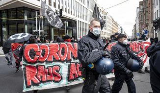 """Various initiatives and left-wing groups demonstrate against a demo of right-wing extremists and so-called """"Reichsbuerger"""" in Berlin, Germany, Saturday, March 20, 2021. Right-wing extremists and """"Reich citizens"""" are demonstrating around the Brandenburg Gate today. (Fabian Sommer/dpa via AP)"""
