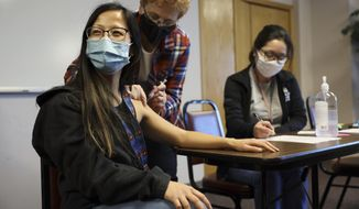 """Lisa Xiong, a staff member at The Hmong Institute, gets her first dose of the Moderna COVID-19 vaccine at a clinic at Life Center in Madison, Wis., on March 9, 2021. """"It wasn't as bad as I thought,"""" she said after Laurel Losenegger, a volunteer nurse with the Benevolent Specialists Project, delivered the shot. (Coburn Dukehart/Wisconsin Watch via AP)"""