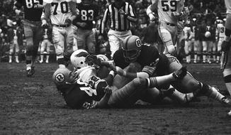 Philadelphia Eagle Cyril Pinder (22) is caught between two Washington Redskins, Jon Jaqua, bottom, and Russell Tillman, during first quarter action at RFK Stadium, Dec. 13, 1970, Washington, D.C. (AP Photo/John Duricka) **FILE**