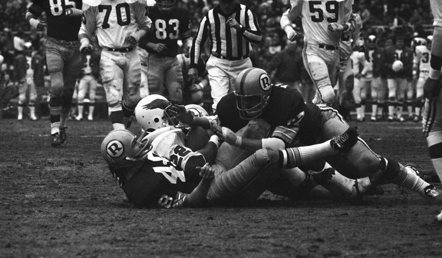 Philadelphia Eagle Cyril Pinder (22) is caught between two Washington Redskins, Jon Jaqua, bottom, and Russell Tillman, during first quarter action at RFK Stadium, Dec. 13, 1970, Washington, D.C. (AP Photo/John Duricka) **FILE**