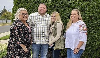 In this photo taken in October 2020, Jennifer Lannon, second from right, poses for a photo with her brother Chris Whitman, second from left, and sisters, Sarah Whitman, far left, and Kim Bermudez in Blackwood, N.J. Lannon's body and three other people were found in a vehicle in a parking garage at Albuquerque International Sunport, New Mexico's largest airport, on March 5. Her ex-husband, 47-year-old Sean Lannon of Grants, New Mexico, said he confessed to killing16 killings in all, including the four found at the airport. (Sharon Whitman via AP)