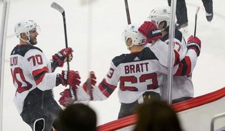 New Jersey Devils' Jesper Bratt (63) celebrates with teammates Dmitry Kulikov (70) and Pavel Zacha, right, after scoring the game winning goal against the Pittsburgh Penguins during overtime of an NHL hockey game, Sunday, March 21, 2021, in Pittsburgh. The Devils won 2-1. (AP Photo/Keith Srakocic)