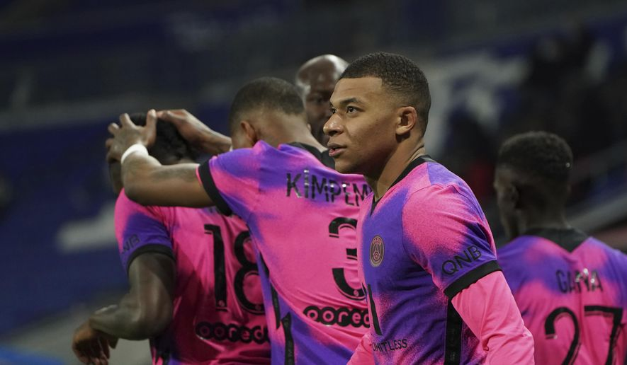 Paris Saint Germain's Kylian Mbappe looks on after he scored a goal against Lyon during the French League One soccer match between Lyon and PSG in Decines, near Lyon, central France, Sunday, March 21, 2021. (AP Photo/Laurent Cipriani)