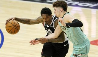 Los Angeles Clippers guard Lou Williams, left, tries to drive past Charlotte Hornets guard LaMelo Ball during the second half of an NBA basketball game Saturday, March 20, 2021, in Los Angeles. The Clippers won 125-98. (AP Photo/Mark J. Terrill)