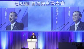 Japanese Prime Minister and ruling Liberal Democratic Party (LDP) leader Yoshihide Suga delivers a speech at the annual party convention in Tokyo Sunday, March 21, 2021. Suga pledged Sunday to do his utmost to prevent a resurgence of the coronavirus ahead of the Olympic torch relay and his upcoming visit to Washington. (Yoshikazu Tsuno/Pool Photo via AP)