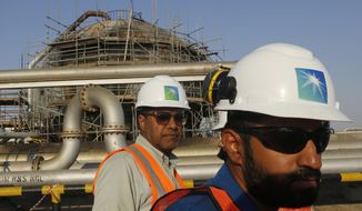 In this Sept. 20, 2019, file photo, engineers walk in front of an oil separator at a Saudi Aramco processing facility in Abqaiq, Saudi Arabia. Saudi Arabia's state-backed oil giant Aramco announced Sunday, March 21, 2021, that its 2020 profits fell sharply in 2020 to $49 billion, a big drop that came as the coronavirus pandemic roiled global energy markets. (AP Photo/Amr Nabil, File)