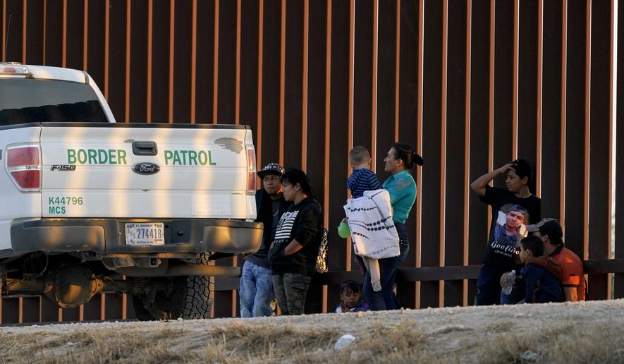 A U.S. Customs and Border Protection vehicle is seen next to migrants after they were detained and taken into custody, Sunday, March 21, 2021, in Abram-Perezville, Texas. A surge of migrants on the Southwest border has the Biden administration on the defensive. The head of Homeland Security acknowledged the severity of the problem but insisted it's under control and said he won't revive a Trump-era practice of immediately expelling teens and children. (AP Photo/Julio Cortez)