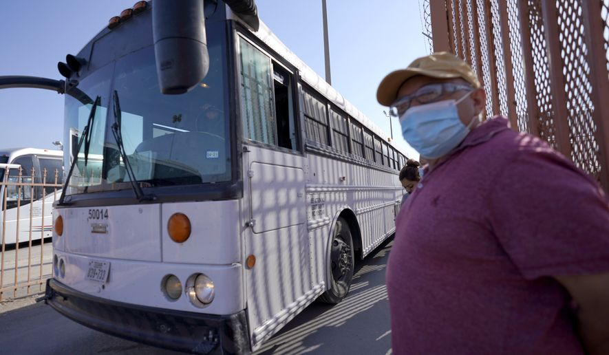 A bus drives near a man waiting in line to cross into the United States on the McAllen-Hidalgo International Bridge as a bus leaves after deporting a group of migrants, Saturday, March 20, 2021, in Hidalgo, Texas. (AP Photo/Julio Cortez)