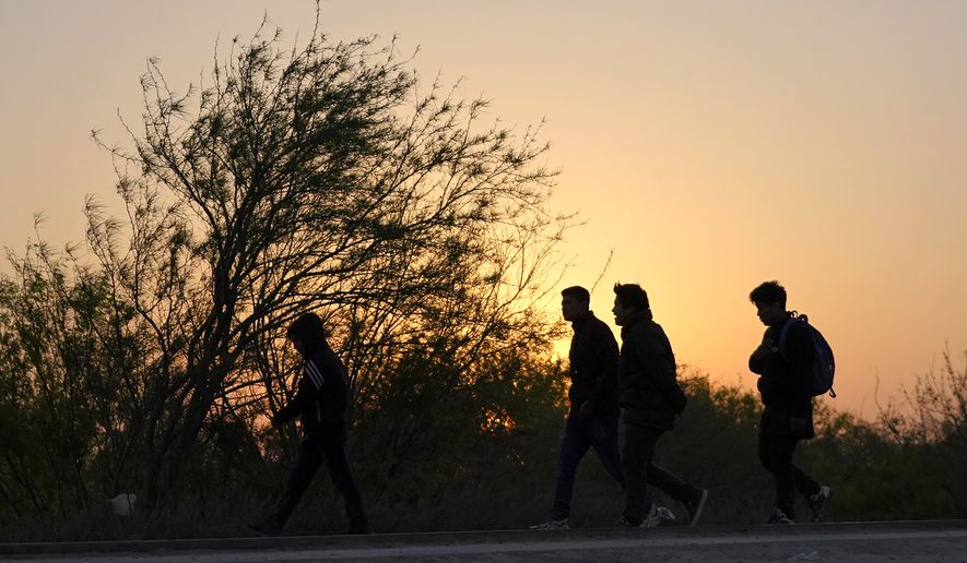 Migrants walk near a gate on the U.S.-Mexico border wall after they were spotted by a U.S. Customs and Border Protection agent and taken into custody while trying to cross, Sunday, March 21, 2021, in Abram-Perezville, Texas. The fate of thousands of migrant families who have recently arrived at the Mexico border is being decided by a mysterious new system under President Joe Biden. U.S. authorities are releasing migrants with acute vulnerabilities and allowing them to pursue asylum. But its not clear why some are considered vulnerable and not others. (AP Photo/Julio Cortez)