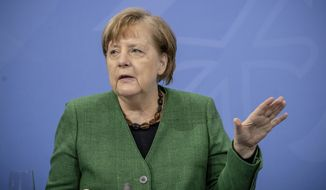 German Chancellor Angela Merkel gestures during a press conference in the Chancellor's Office following consultations between the federal and state governments in Berlin Tuesday, March 23, 2021. Germany extended its lockdown measures by another month and imposed several new restrictions, including largely shutting down public life over Easter, in an effort to drive down the rate of coronavirus infections. (Michael Kappeler/Pool Photo via AP)
