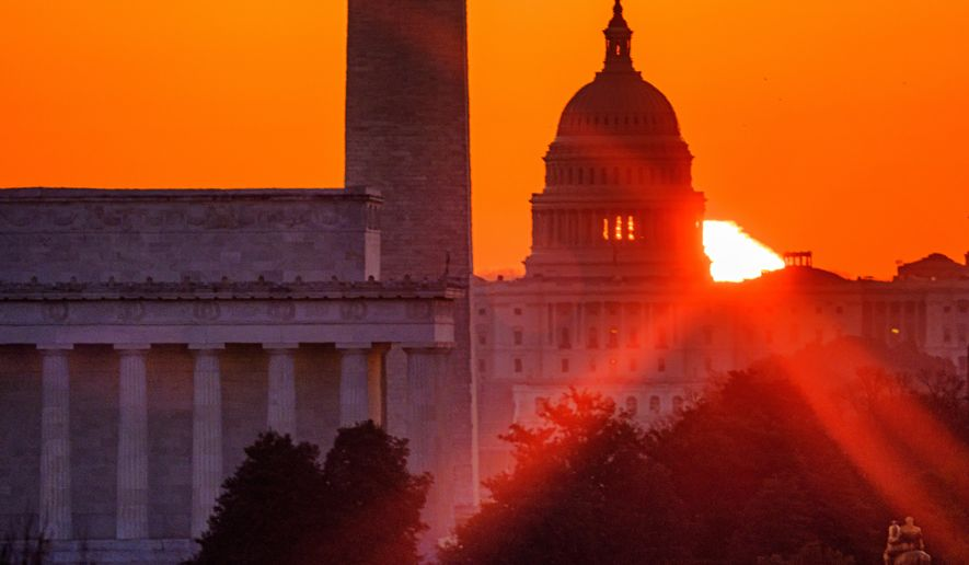 """The sun flares through the camera lens as it rises behind the U.S. Capitol building, Washington Monument and the Lincoln Memorial, Monday, March 22, 2021, in Washington. Talk-radio host Michael Savage warns that the push during former President Barack Obama's era for """"hope and change"""" has intensified. (AP Photo/J. David Ake)"""