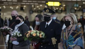 Representatives of victims and others carry flowers and photos at Brussels Airport during events held for the fifth anniversary of the Brussels terrorist attacks, in Brussels, Monday, March 22, 2021. (Stephanie Lecocq, Pool via AP)