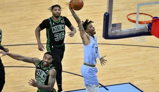 Memphis Grizzlies guard Ja Morant (12) goes up for a dunk against Boston Celtics guard Jeff Teague (55) in the second half of an NBA basketball game Monday, March 22, 2021, in Memphis, Tenn. (AP Photo/Brandon Dill)