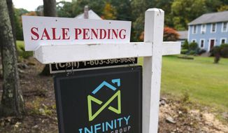 FILE - In this Sept. 29, 2020 file photo, a sale pending sign is displayed outside a residential home for sale in East Derry, N.H. Sales of previously occupied U.S. homes slowed last month as rising prices and a dearth of homes for sale kept some would-be buyers on the sidelines.  (AP Photo/Charles Krupa, File)