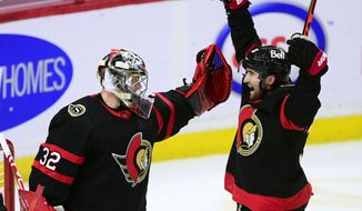 Ottawa Senators' Filip Gustavsson (32) celebrates with Colin White (36) after the team's win over the Calgary Flames in an NHL hockey game in Ottawa, Ontario, Monday, March 22, 2021. (Sean Kilpatrick/The Canadian Press via AP)