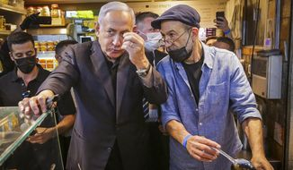Israeli Prime Minister Benjamin Netanyahu, center left, tours the Mahane Yehuda market while campaigning a day before national elections, in Jerusalem, Monday, March 22, 2021. The March 23 vote is Israel's fourth parliamentary election in two years. (AP Photo/Oren Ben Hakoon)
