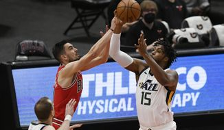 Utah Jazz's Derrick Favors (15) and Chicago Bulls' Tomas Satoransky reach for a rebound during the first half of an NBA basketball game Monday, March 22, 2021, in Chicago. (AP Photo/Paul Beaty)