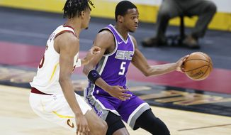 Sacramento Kings' De'Aaron Fox (5) passes against Cleveland Cavaliers' Isaac Okor (35) in the second half of an NBA basketball game, Monday, March 22, 2021, in Cleveland.  (AP Photo/Ron Schwane)