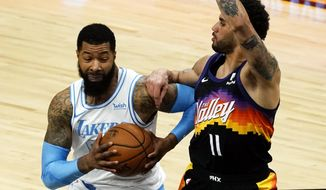 Los Angeles Lakers forward Markieff Morris, left, drives on Phoenix Suns forward Abdel Nader (11) during the first half of an NBA basketball game, Sunday, March 21, 2021, in Phoenix. (AP Photo/Rick Scuteri)
