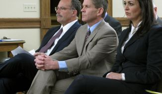 FILE - In this Nov. 13, 2018 file photo, then-Montana Secretary of State Corey Stapleton is flanked by his elections director Dana Corson and then-deputy secretary Christi Jacobsen, as they wait to testify before a legislative committee in Helena, Mont. Jacobsen, a Republican and now the secretary of state, has requested legislation that would allow anyone to bring forward a petition to gather signatures and qualify a minor party for the ballot, even if they were not affiliated with the party. (AP Photo/Matt Volz,File)