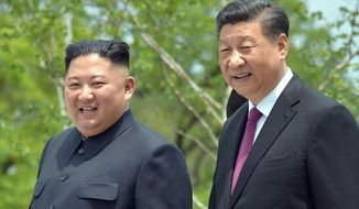 """In this June 21, 2019, file photo provided by the North Korean government, North Korean leader Kim Jong-un, left, and Chinese President Xi Jinping stroll in the premises of Kumsusan guest house in Pyongyang, North Korea. Kim in a message to Xi called for stronger """"unity and cooperation"""" between the countries in the face of challenges posed by """"hostile forces,"""" the North's state media and Tuesday, March 23, 2021. (Korean Central News Agency/Korea News Service via AP, File)"""