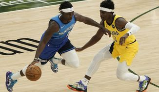 Milwaukee Bucks' Jrue Holiday is fouled by Indiana Pacers' Aaron Holiday during the first half of an NBA basketball game Monday, March 22, 2021, in Milwaukee. (AP Photo/Morry Gash)