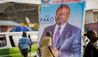 """FILE- In this Sunday March 7, 2021 file photo, people walk past an election poster featuring opposition presidential candidate Guy Brice Parfait Kolelas, in downtown Brazzaville, Congo. Kolelas, who was hospitalized with COVID-19 complications on election day, has died, a spokesman said Monday, March 22, 2021. The 61-year-old politician was last seen in a video circulating Saturday on social media in which he told supporters he was """"fighting death."""" Aides later said he was been flown to France for further treatment. Spokesman Justin Nzoloufoua confirmed his death Monday to The Associated Press. (AP Photo/Lebon Chansard Ziavoula, File)"""