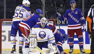 New York Rangers' Chris Kreider (20), right, celebrates his second goal of an NHL hockey game in the third period on a power-play against Buffalo Sabres' Dustin Tokarski (31) during an NHL hockey game Monday, March 22, 2021, in New York. (Bruce Bennett/Pool Photo via AP)