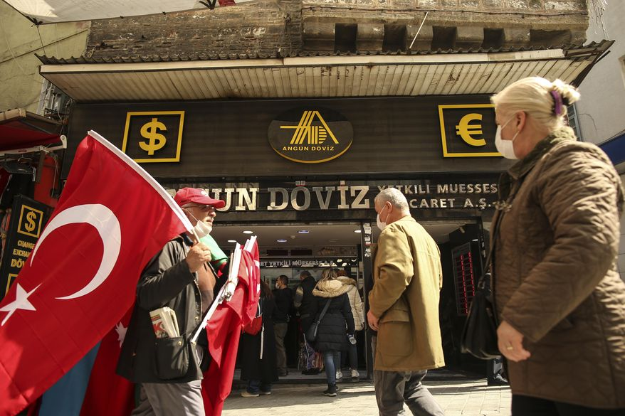 A vendor offering Turkish flags for sale walks past a currency exchange shop, at an open market Istanbul, Monday, March 22, 2021. The Turkish currency plummeted against the U.S. dollar on Monday after President Recep Tayyip Erdogan fired the central bank governor over the weekend for hiking interest rates. The lira was trading at around 7.9 against the dollar — nearly 10% down from Friday's close. Erdogan, who advocates keeping interest rates low to tame inflation, unexpectedly fired Naci Agbal with a decree on Saturday, just four months after he took office. (AP Photo/Emrah Gurel)
