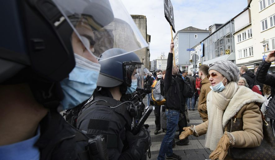 """A woman speaks to police officers on duty at a rally under the motto """"Free citizens Kassel - basic rights and democracy"""" in Kassel, Germany, Saturday, March 20, 2021. According to police, several thousand people were on the move in the city center and disregarded the instructions of the authorities during the unregistered demonstration against Corona measures. (Swen Pfoertner/dpa via AP)"""