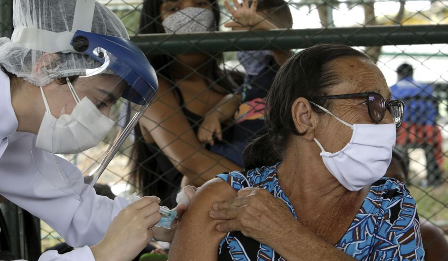 A health worker inoculates a woman at a COVID-19 vaccination point for priority elderly persons in the Ceilandia neighborhood, on the outskirts of Brasilia, Brazil, Monday, March 22, 2021. (AP Photo/Eraldo Peres)