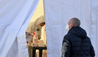 Polish commuters stands in front of a tent and waits for a coronavirus test at the Stadtbruecke border crossing between Germany and Poland in Frankfurt an der Oder, Germany, Monday, March, 22, 2021. Poland is being classified as a 'high risk' COVID-19 area by German authorities and people crossing into Germany from Poland must provide a negative coronavirus test. (Patrick Pleul/dpa via AP)