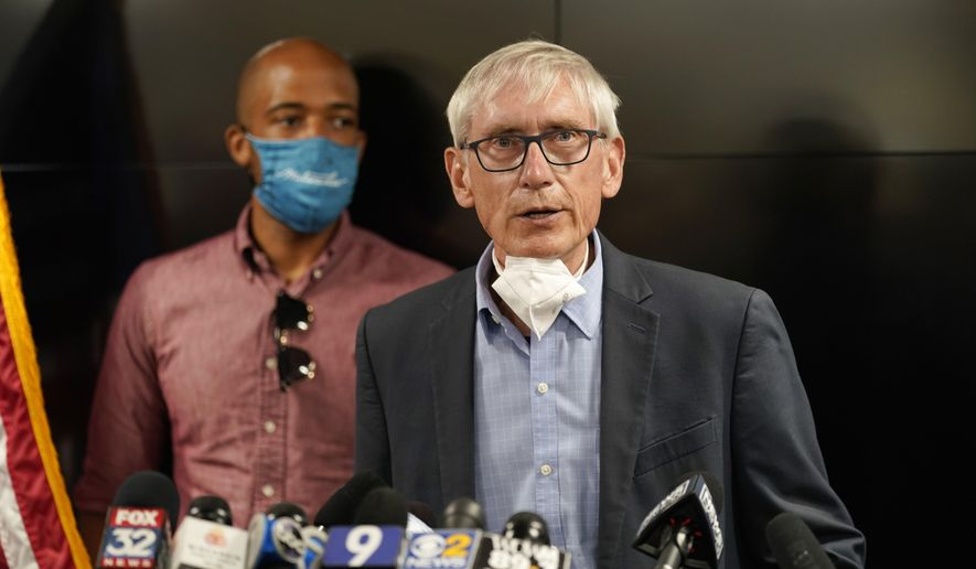 FILE - In this Thursday, Aug. 27, 2020, file photo, Wisconsin Gov. Tony Evers speaks during a news conference in Kenosha, Wis., as Lt. Gov. Mandela Barnes stands at rear. The fight over control of Wisconsin's share of the $1.9 trillion federal coronavirus stimulus package ramps up Tuesday, March 23, 2021, in the state Legislature, with Republicans voting on a bill to take away Evers' ability to decide how to spend the estimated $5.7 billion coming for state and local governments. (AP Photo/Morry Gash, File)