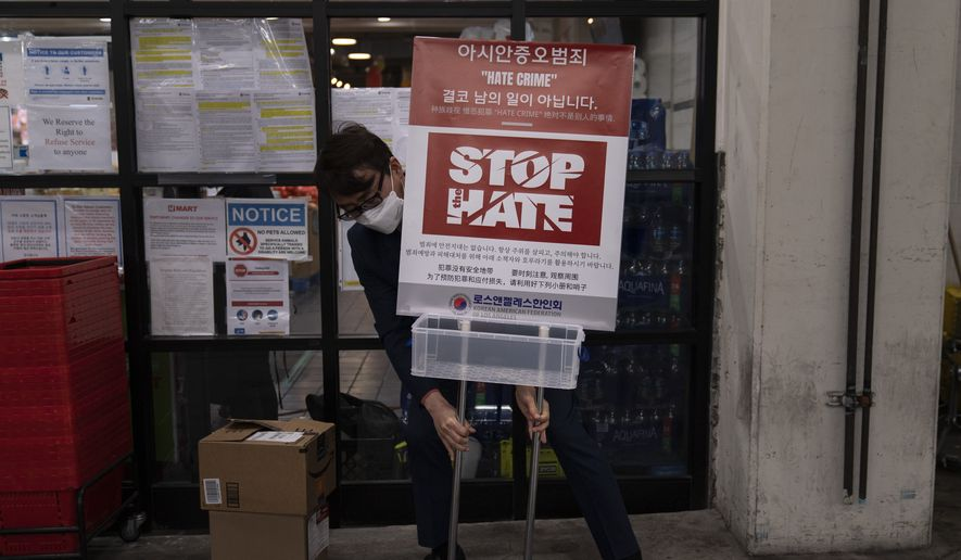 Peter Chang from the Korean American Federation of Los Angeles places a poster to bring awareness to anti-Asian hate crimes Tuesday, March 23, 2021, in the Koreatown neighborhood of Los Angeles. (AP Photo/Jae C. Hong)